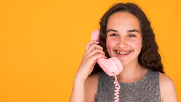 Girl talking on a pink telephone with copy space