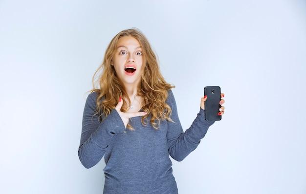 Девушка разговаривает по телефону и удивляется.