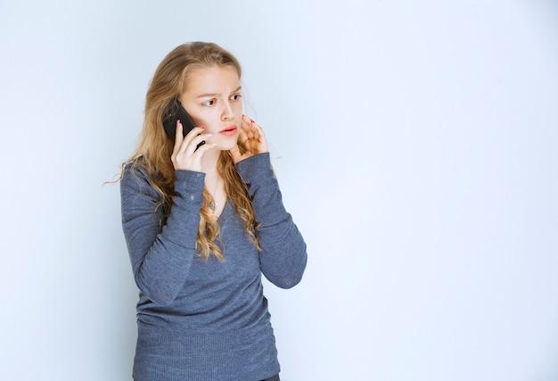 Девушка разговаривает по телефону и выглядит напуганной.