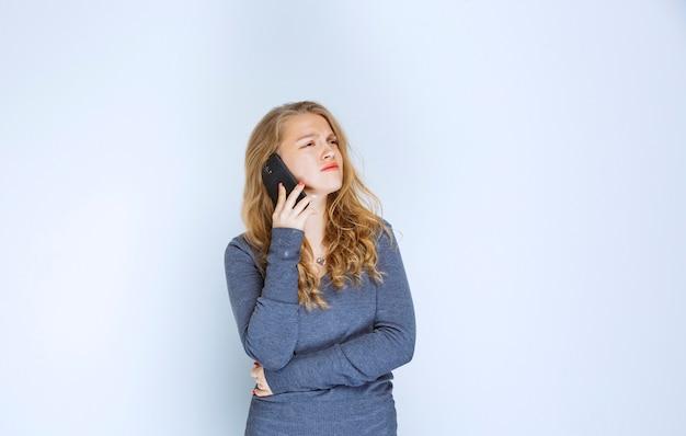 Девушка разговаривает по телефону без какой-либо реакции.