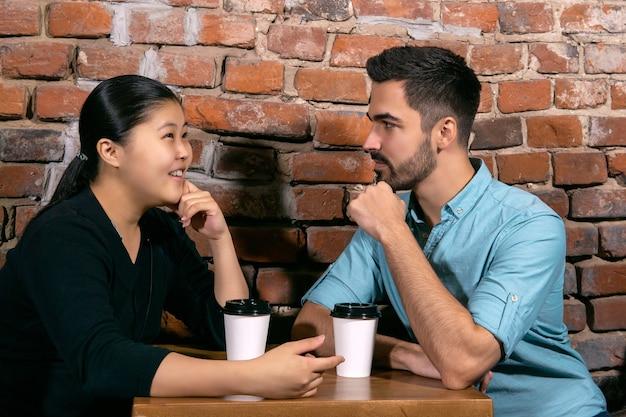 彼らが荒いレンガの壁の背景にあるカフェのテーブルに座っている間、女の子は若い男に何かについて話します