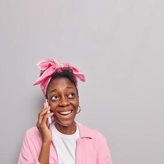 Девушка разговаривает по мобильному телефону с положительным выражением лица отвечает на телефонные звонки звонки по сотовой связи лучший друг носит розовую куртку, платок, повязанный на голове, стоит в помещении