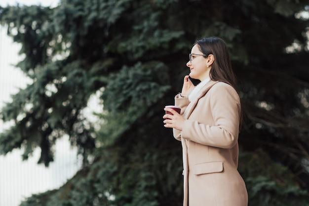 Девушка разговаривает по телефону в парке у сосны