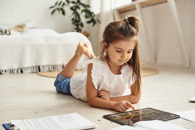 The girl teaches lessons and plays on the tablet at home