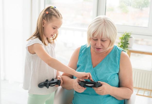ジョイスティックで遊ぶことをおばあちゃんに教える女の子