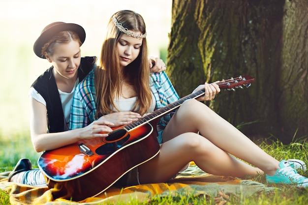 公園でギターを弾くように友達に教える女の子