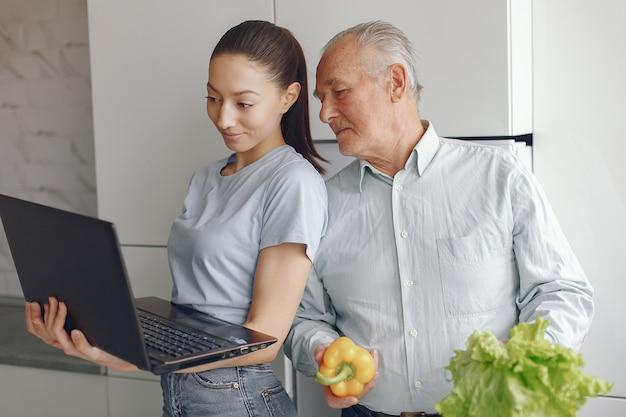 Девушка учит дедушку пользоваться ноутбуком