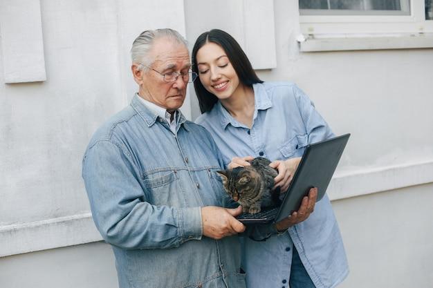 ノートパソコンの使い方を祖父に教える女の子