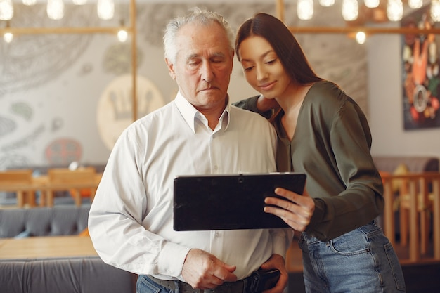 祖父にタブレットの使い方を教える女の子