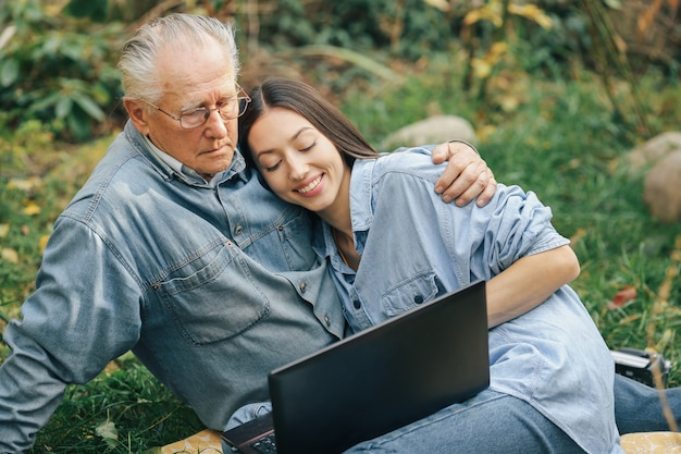 Girl teaching her grandfather how to use a laptop