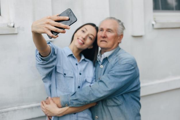 Ragazza che insegna a suo nonno come usare un telefono