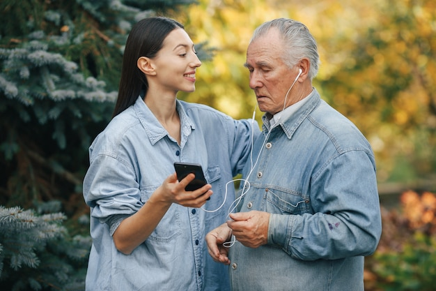 Girl teaching her grandfather how to use a phone