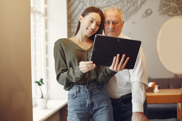 Girl teaching her grandfather how to use a tablet