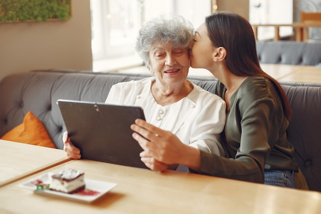 Girl teaching her grandmother how to use a tablet