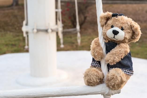 Girl teddy bear hanging in playground