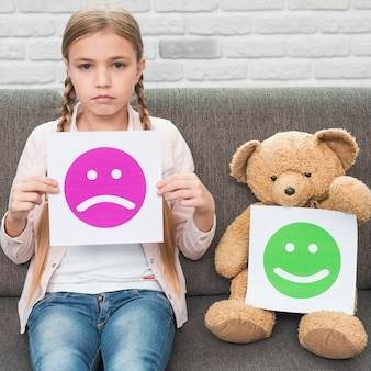 Girl and teddy bear holding sad and happy face emoticons paper sitting on sofa