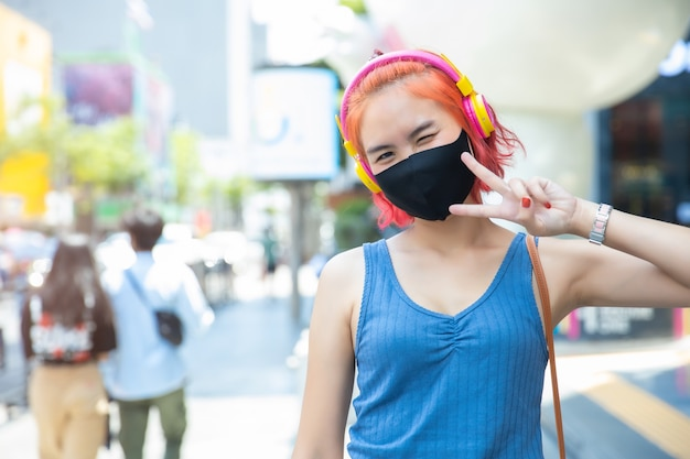 Girl teen cute punk hipster style red hair color wear face mask or face shield at outdoor public shopping walking street.