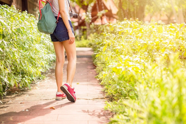 Girl teen travel walking in the nature footpath, women tourist walking with hat backpack bag