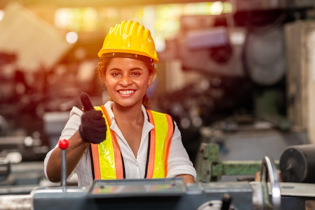 Girl teen worker with safety helmet show thumb up working as labor in industry factory with steel machine.