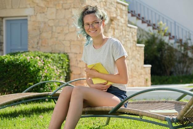 Девушка-подросток 15, 16 лет сидит на шезлонге на лужайке, пишет карандашом в тетради. снова в школу, летнее начало занятий