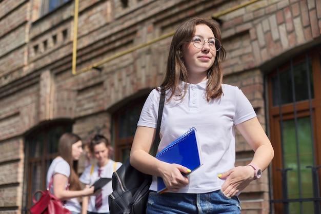 Студент колледжа подростка девушки представляя открытый в белой футболке. фон кирпичное здание, группа студенток. начало занятий, возвращение в колледж, копия пространства