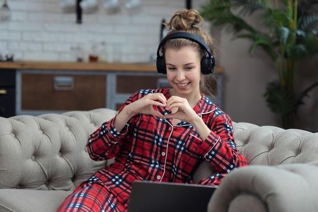 Девушка-подросток общается в социальных сетях или в видеочате, делая знак сердца, сидя на диване у себя дома