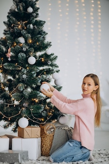 Девушка подросток украшает елку