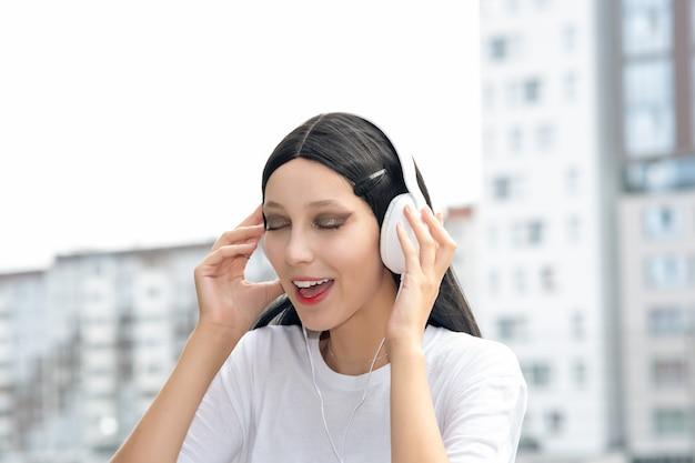 女の子のティーンエイジャーは、街の背景に屋外でヘッドフォンで音楽を楽しんでいます