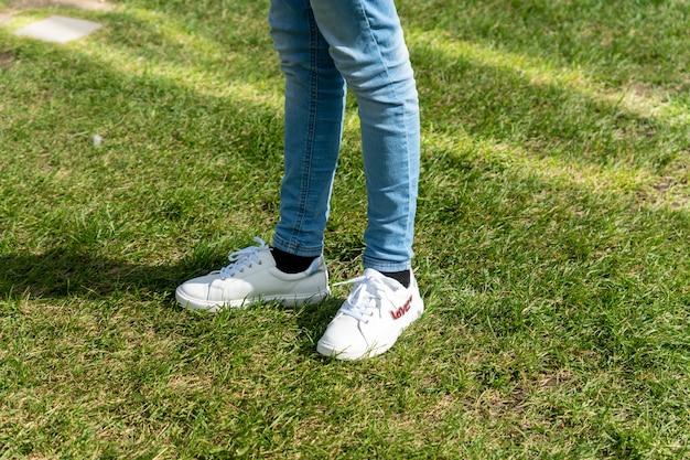 Девушка подростковой моды. джинсы скинни и белые кроссовки. повседневный вид. летняя прогулка.