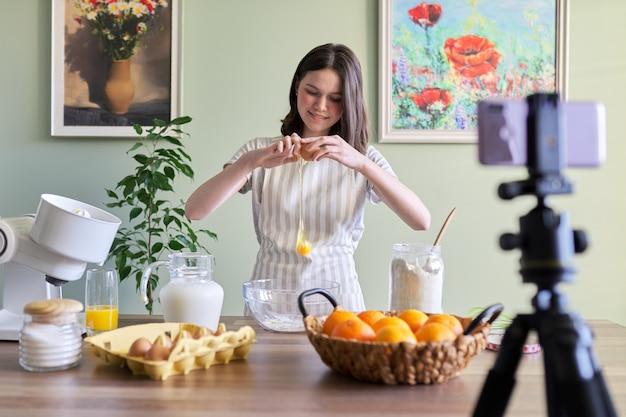 キッチンで自宅でオレンジ色のパンケーキを調理する女の子のティーンエイジャーの食品ブロガー。原材料は小麦粉、オレンジ、牛乳、砂糖、卵を割る製品です。料理の趣味の女の子、10代、子供たちのフォロワーチャンネル