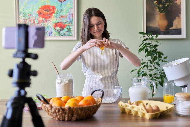 Girl teenager food blogger cooking orange pancakes at home in kitchen. ingredients products flour, oranges, milk, sugar, breaks eggs. cooking hobbies girls, teens and children followers channel
