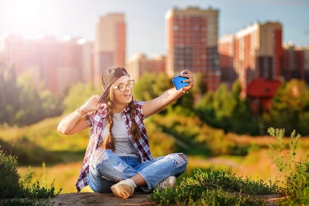 メガネで10代の女の子が地面の街の背景に座っています。
