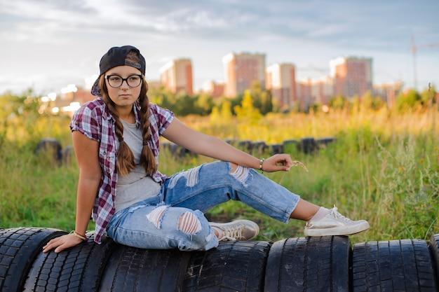 メガネの10代の少女は、selfieスマートフォンのヘッドフォンで地上都市に座っています。
