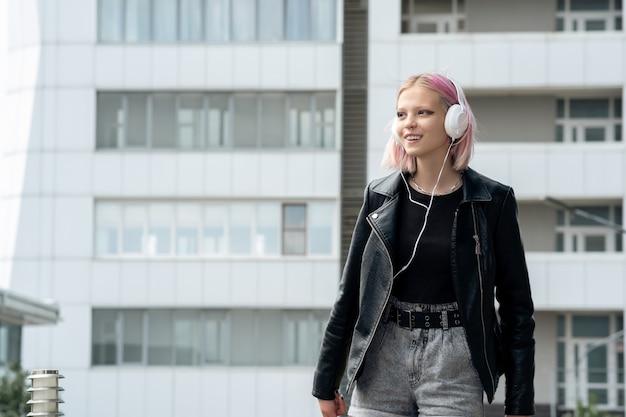 街を歩いているヘッドフォンで音楽を聴いている10代の少女