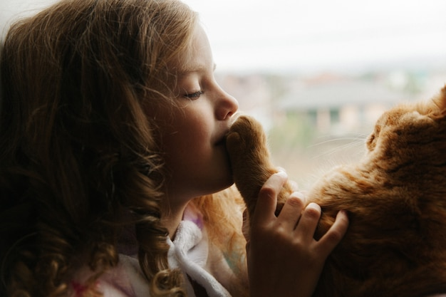 10代の少女は、家の窓のパジャマに座って、生姜猫を抱いています。家にいる。