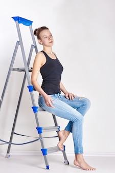 Девушка-подросток сидит на лестнице. молодая модель позирует на светлой стене. естественная красота, маленький ребенок