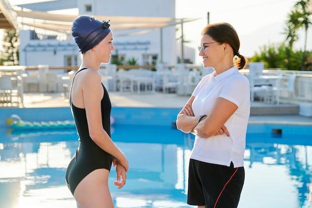 屋外プールの近くの女性トレーナーとスポーツ水着キャップの女の子ティーンエイジャースイマー、若者のアクティブな健康的なライフスタイル