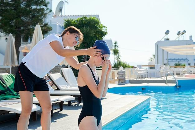 Девушка-подросток-пловец в спортивной кепке купальника с женщиной-тренером возле открытого бассейна, активный здоровый образ жизни молодежи