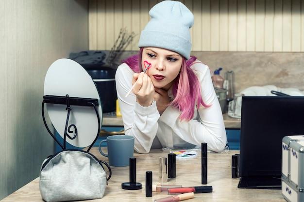 ピンクの髪の少女ティーンエイジャーは、鏡の前で自宅で明るい化粧をします。