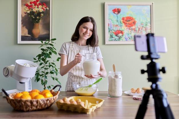 소녀 십대 젊은 음식 블로거는 오렌지 팬케이크를 요리하고, 우유를 붓고, 웹 카메라에 조리법을 기록합니다. 집에서 맛있고 건강한 음식을 요리하는 여자, 십대 취미