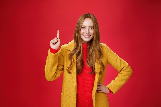 最初の理由を言う女の子は彼女のアドバイスを使用します。キュートでフレンドリーな元気いっぱいの黄色いコートを着た若い赤毛の女性は、手を上げてナンバーワンを示し、赤い背景に対してカメラで広く笑っています。