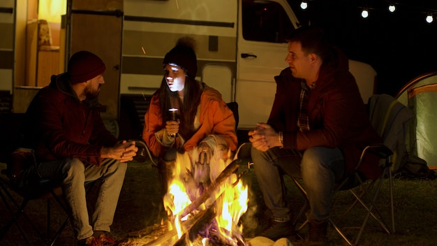Girl telling a scary story to her friends around camp fire in cold night of autumn. retro camper van. light bulbs