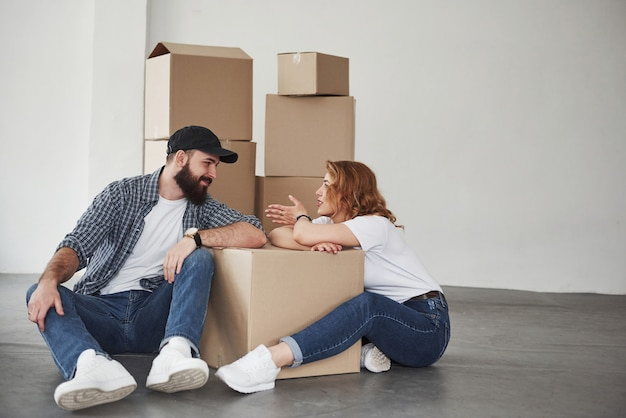 女の子は面白いことを話します。彼らの新しい家で一緒に幸せなカップル。引っ越しの発想