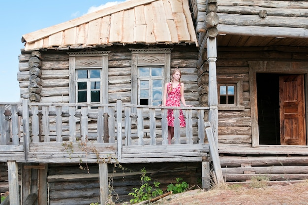 Girl on the terrace of an old wooden house