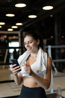 Girl texting while taking a break in a gym. reads a message