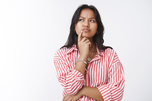 Girl think deeply having assumptions. portrait of thoughtful determined serious-looking young wise woman frowning looking focused while making decision, standing doubtful over white background