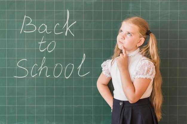 Girl thinking standing near blackboard