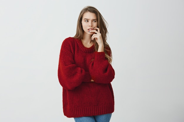 Girl thinks how to solve problem. studio shot of beautiful caucasian girl with fair hair, wearing trendy loose sweater, looking aside while touching chin, planning something or worrying