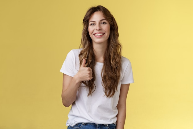 Girl thinks you done great job. smiling cheerful good-looking woman long curly haircut approve perfect choice give thumb up agree like your style grinning support excellent idea yellow background