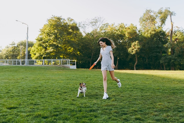 緑の草の上でそれを捕まえる小さな面白い犬にオレンジ色のフライングディスクを投げる女の子。公園で屋外で遊ぶリトルジャックラッセルテリアのペット。野外で犬と飼い主。